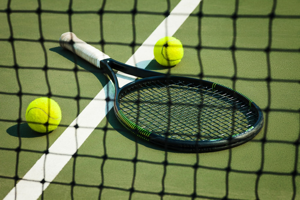 Tennisschläger und Tennisbälle liegen auf dem Court