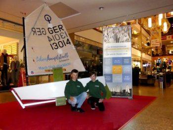 Ist nach 30 Jahren auch in der Schweriner Innenstadt angekommen und macht Werbung für den Segelsport an Land: Der Opti, stolz präsentiert von den Schweriner Seglern Reamon und Noel Theiner im Schlossparkcenter (© Veranstalter).