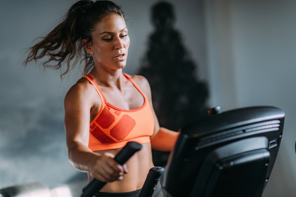 Frau in Sportkleidung trainiert auf einem Crosstrainer