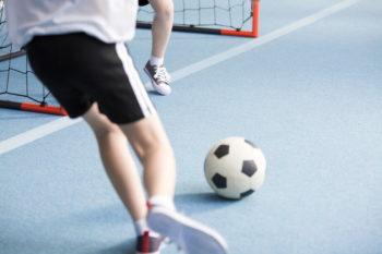 zwei Kinder spielen Fußball in der Halle.