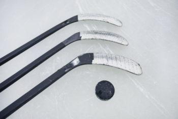 Eishockey: Puck und Hockeyschläger liegen auf der Eisfläche